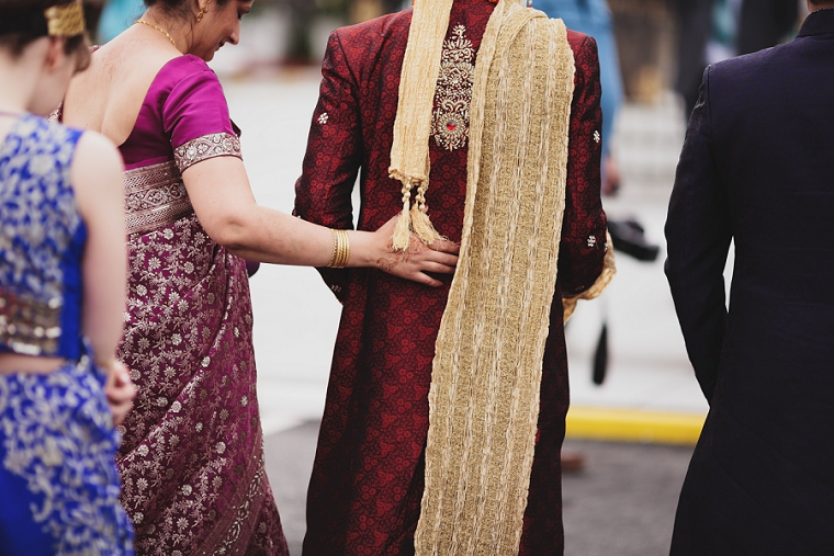 mother of groom places her hand on her sons back at the Gtavesend Gurdwara wedding