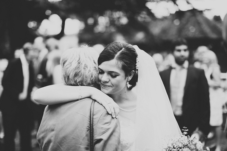 Casual and Candid wedding photograph of bride hugging her guests