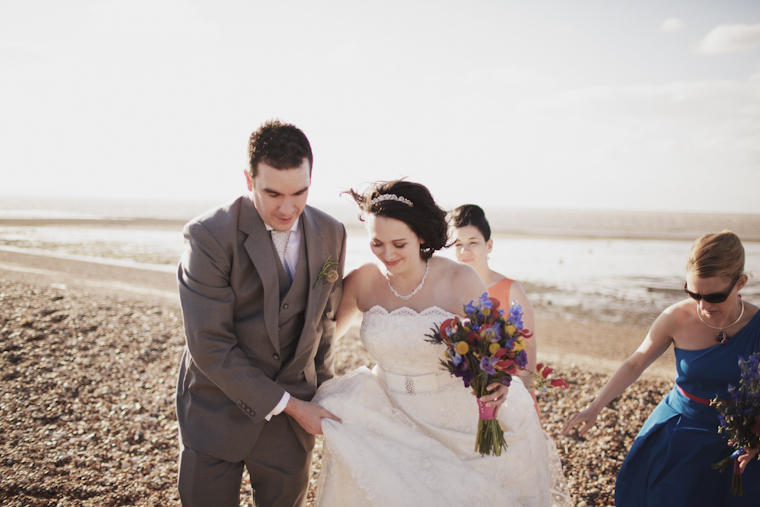Groom helping bride to walk on pebble beach in Whitstable Kent
