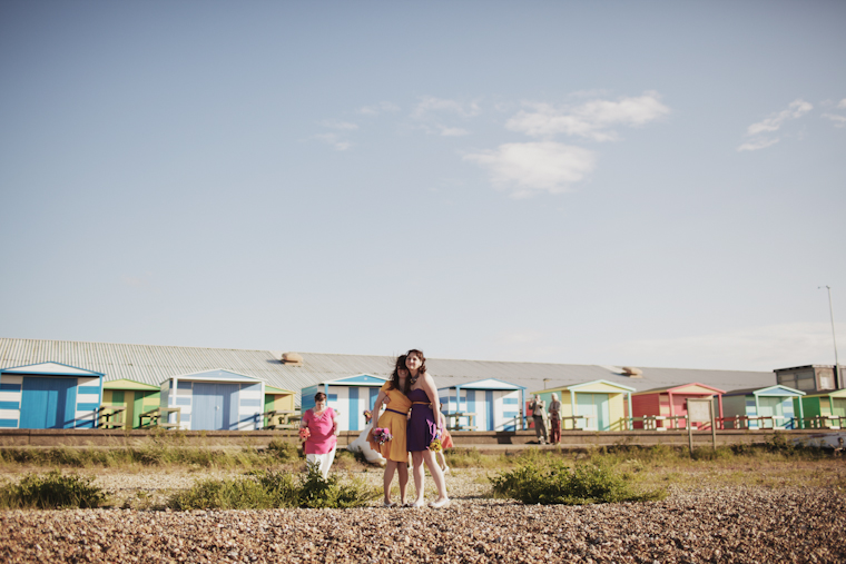 Two bridesmaids hugging on Whitstable beach, Kent