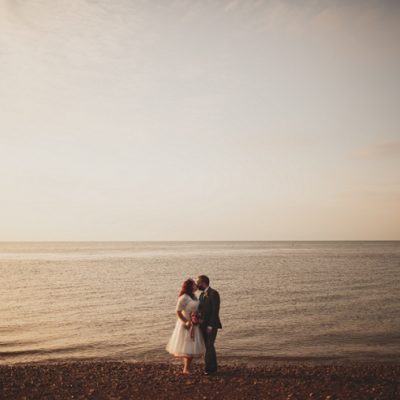 Wedding couple on the beach at sunset at Whitstable in Kent. The Lobster Shack East Quay