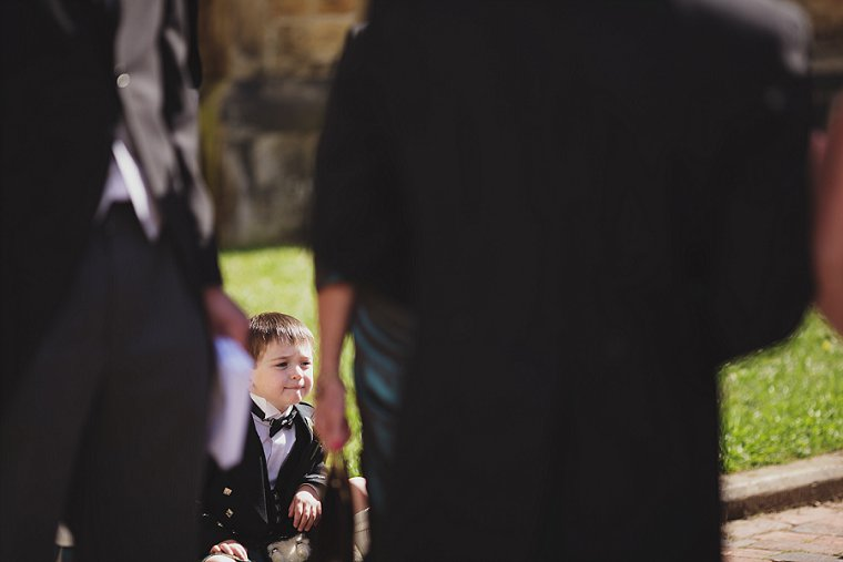 A pageboy sitting quietly looking up at the bride on her wedding day in Tunbridge Wells Kent
