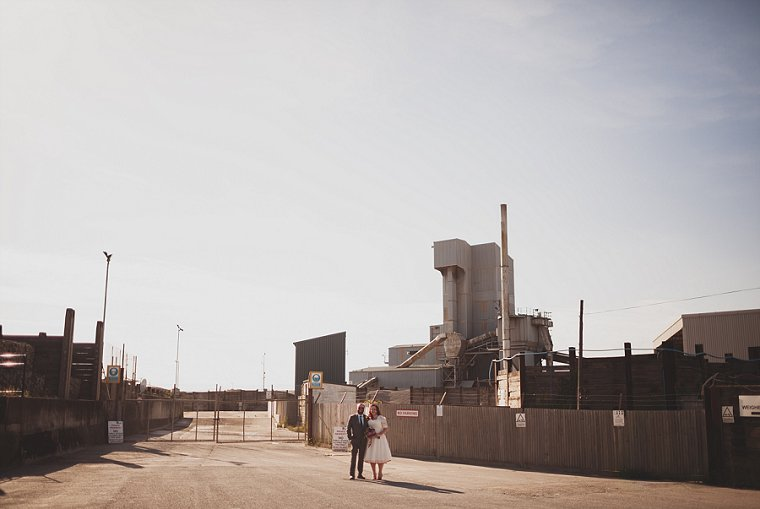 Wedding couple stood outside of a gravel factory in Whitstable after their wedding at the East Quay wedding venue in Whitstable Kent