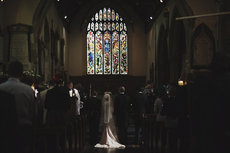 A bride and groom stood in a shaft of light at the alter of a church