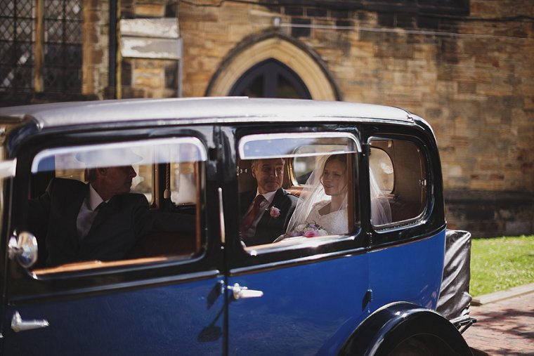 Bride arriving with her father at the church in a vintage car before the start of her wedding at a church in Tunbridge Wells