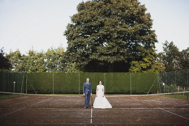 Bride and Groom stood in an old tennis court at Old Kent Barn