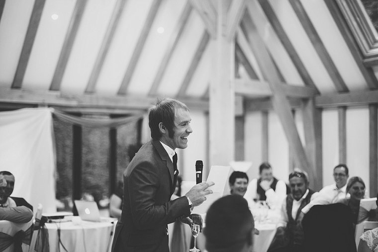 Groom laughing during his wedding speech at the Old Kent Barn