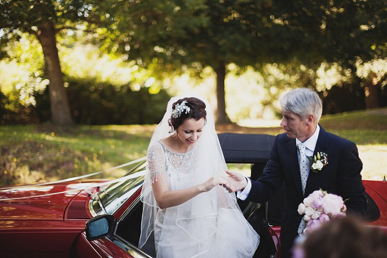 A bride arriving in a red sports car with her father at the church before her wedding at Vigo in Kent