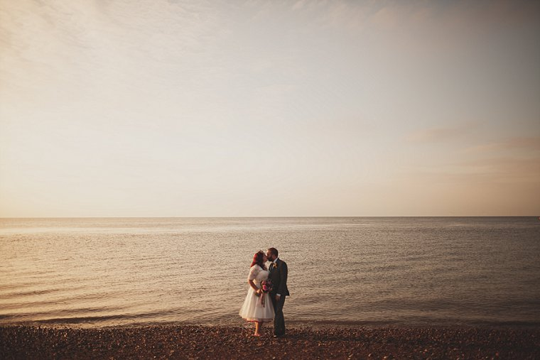 A bride and groom kissing at sunset on the beach at Whitstable in Kent following their wedding at The Lobster Shack East Quay in Kent