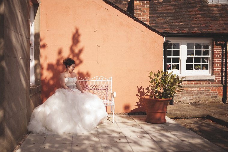 A bride sat on a bench after her wedding. Wedding portrait by Kent Wedding Photographer