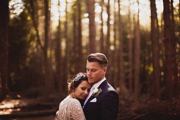 A wedding couple photographed in a forest in Kent hugging