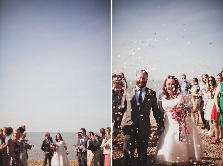 Wedding couple having confetti thrown at them on Whitstable beach in Kent