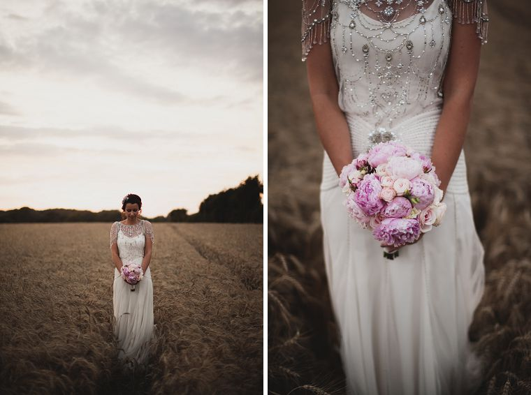 Bride in a wheat field at sunset holding her bouqet photographed by Kent wedding photographer Paul Fuller