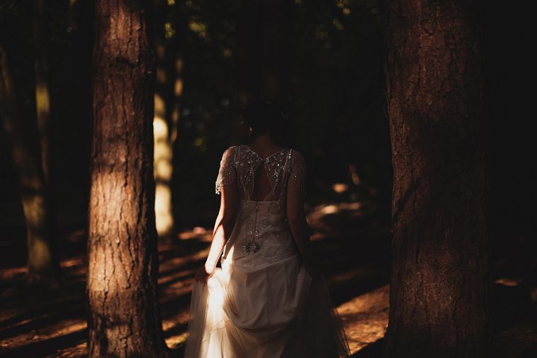 Shafts of light capturing a bride as she walks through a forest in Kent