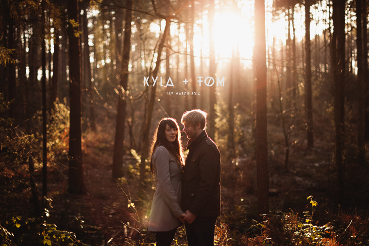 Kyla and Tom stood together on their pre wedding shoot in a sunlit forest at dusk. Photograph is taken at Bedgebury Pinetum and Forest in Tunbridge Wells in Kent