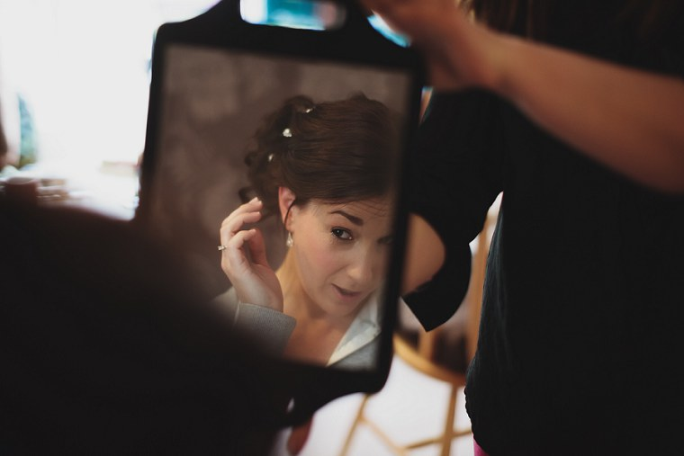 Bride looking at her hair and make up in a hand held mirror