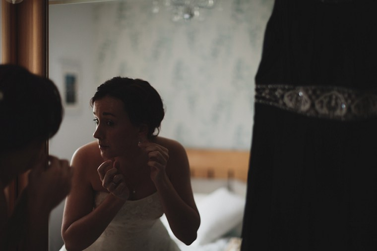 Bride putting on her wedding jewelry in a mirror