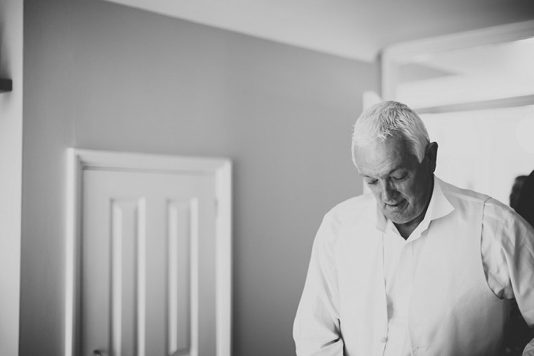 Black and White photograph of brides father as he puts on his wedding suit