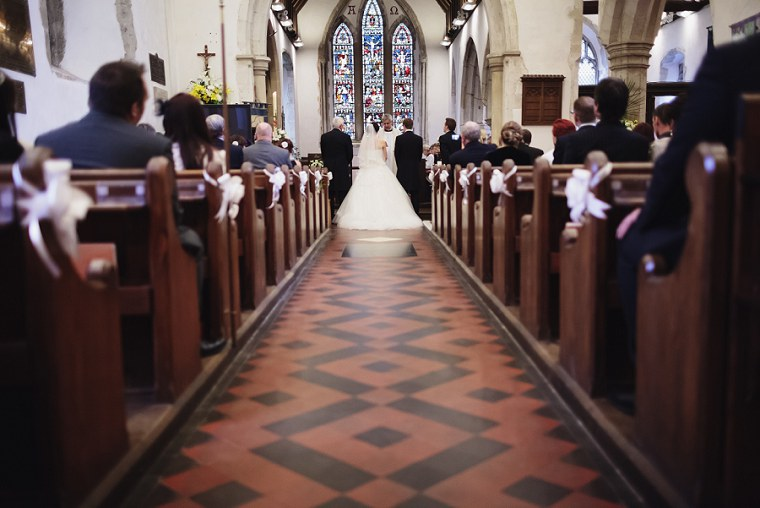 Wide shot from behind of bride and groom as they stand at the altar for their weddingat St Mary's church in Kent