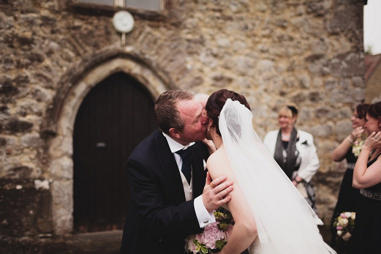 Father of the groom kissing the bide on the cheek after her wedding ceremony at St Mary's Church in Kent
