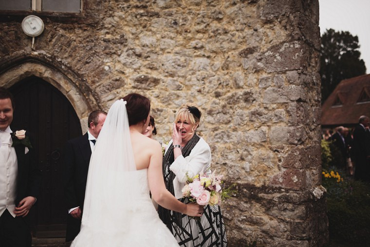 Mother of the groom hugging the bride after her wedding at St Mary's church in Kent