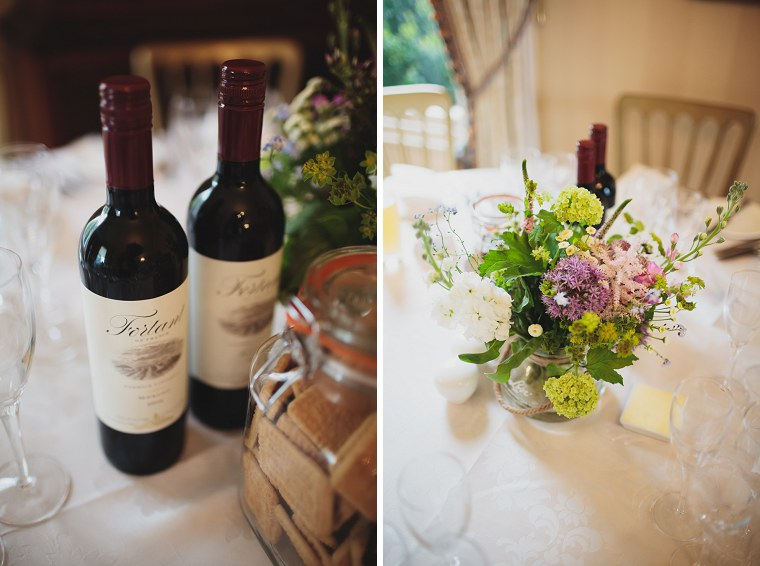 Wedding Flowers and bottles of red wine on the tables at the wedding of Simon and Laura