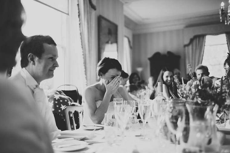 Bride laughing during her fathers wedding speech