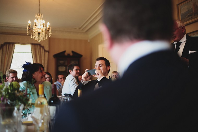 Best man taking a photograph during wedding speeches