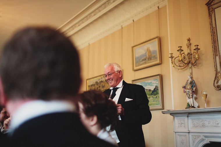 Father of the bride laughing as he gives his speech
