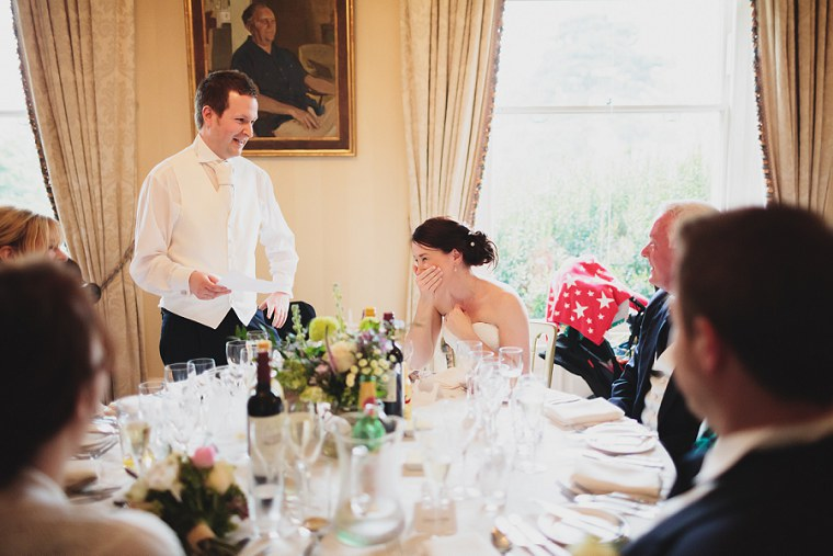 Bride laughing as her husband gives his wedding speech