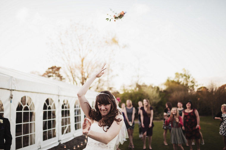 Photo of bride throwing her wedding bouquet at Nettlestead Place