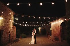 Bride and Groom stood under string lights at Tuscany Wedding