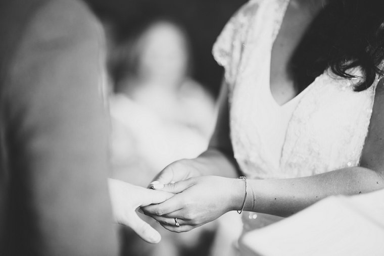 Bride putting wedding ring on the finger of groom