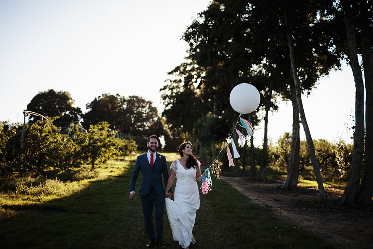 Bride and Groom holding white balloon at their wedding