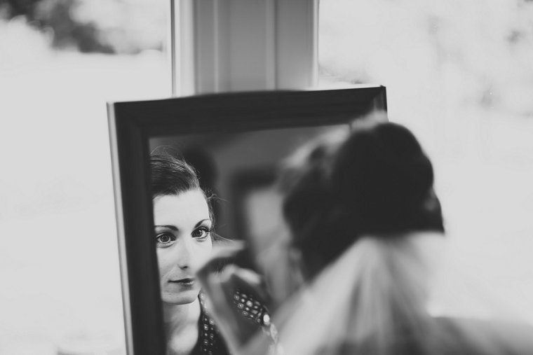Bride looking in to mirror before her wedding at Ratsbury Barn
