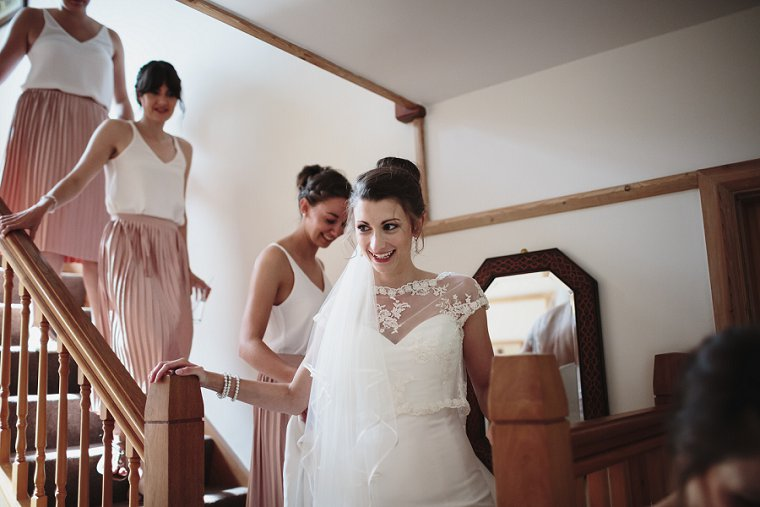 Bride walking down stairs with her bridesmaids before her wedding