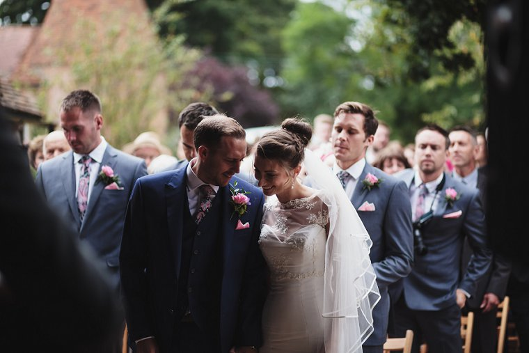 Bride and Groom laughing together during their wedding service at Ratsbury Barn