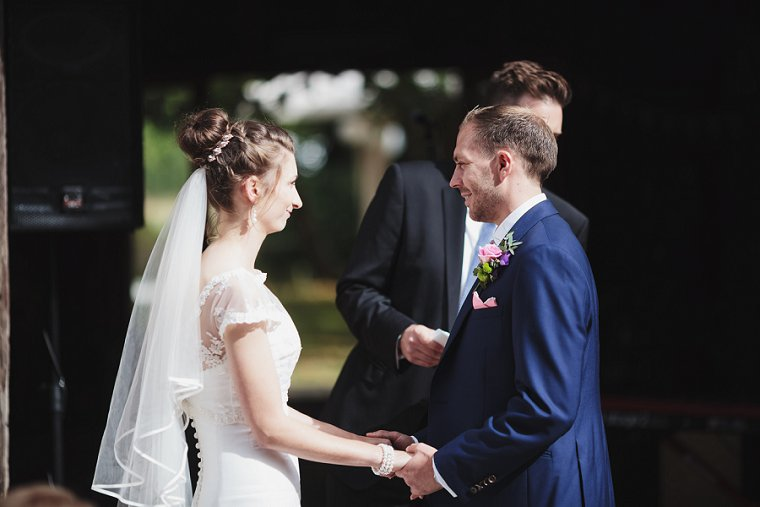 Bride and Groom facing eachother holding hands