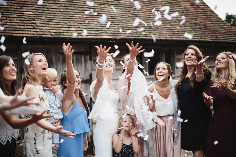 Bride and friends throwing confetti in the air at her wedding at Ratsbury Barn