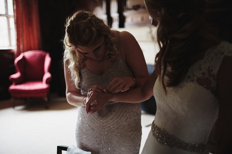 bridesmaid helping bride with her bracelet
