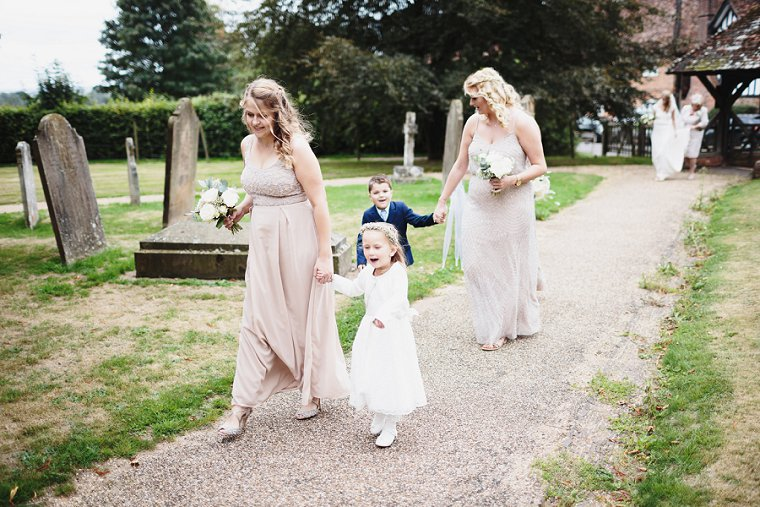 Bridesmaid holding flower girls hand