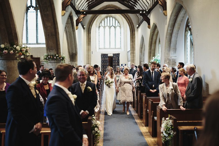 Bride walking down aisle with her mum