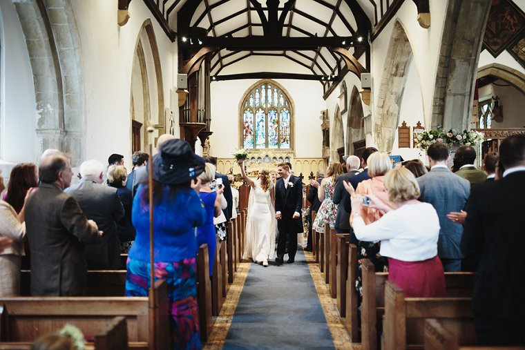 Bride holding her bouquet in the air as she leaves the church