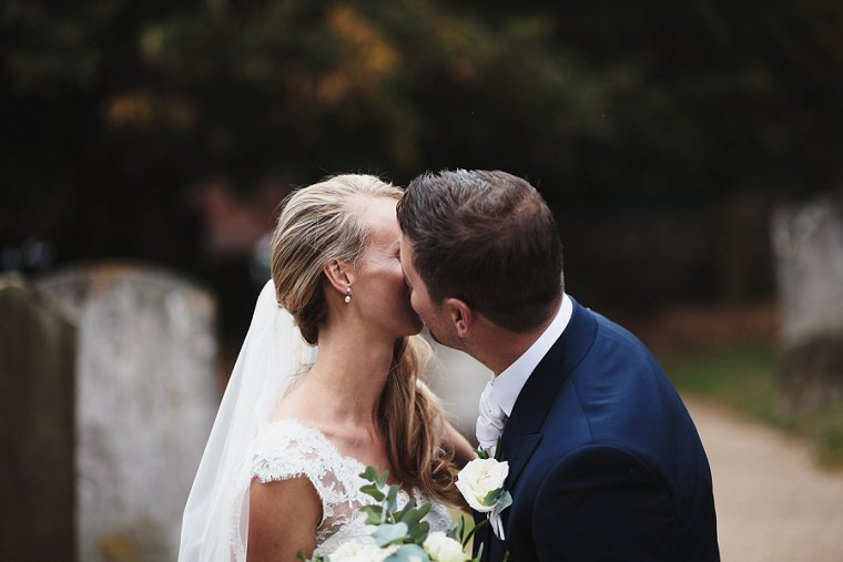 Bride and Groom sharing a kiss outside the church after their Squerryes Court Wedding