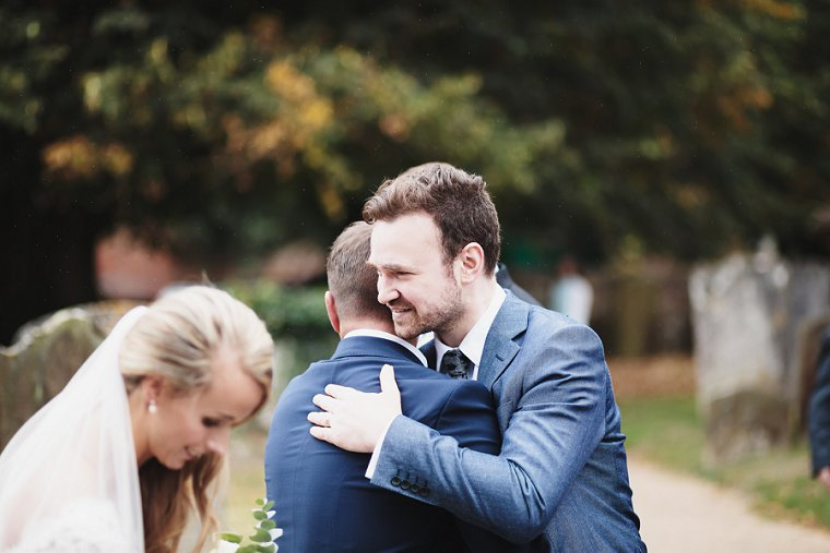 Groom hugging guest