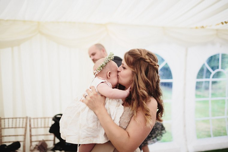 bridesmaid kissing her baby daughter flower girl at Squerryes Court wedding