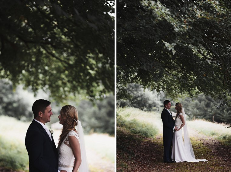 Bride and Groom laughing together under tree during rain on their wedding day