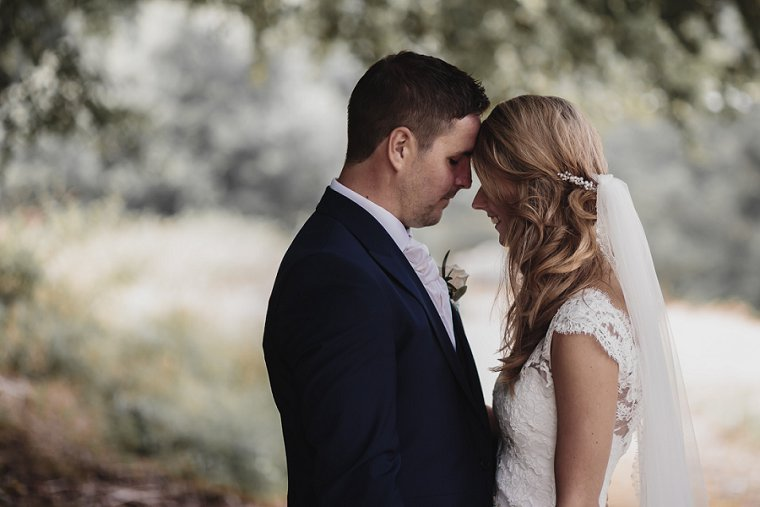 Bride and Groom with eyes closed gently resting their foreheads together