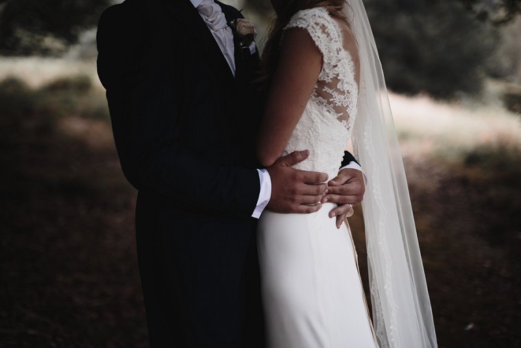 Close up photo of grooms hand on brides waist