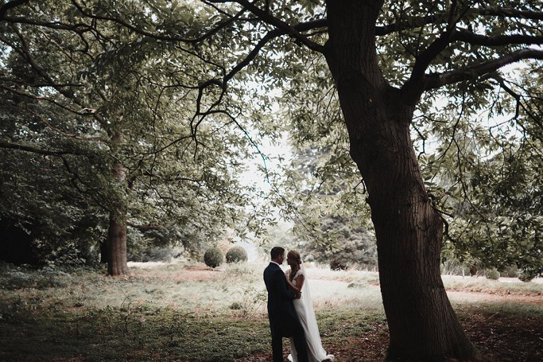 Wedding photography during rain storm at Squerryes Court as Bride and Groom take cover under tree